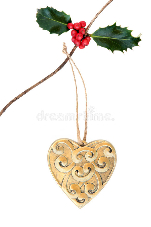 Christmas Heart Decoration. Christmas gold heart decoration with holly hanging on a twig over white background royalty free stock photos