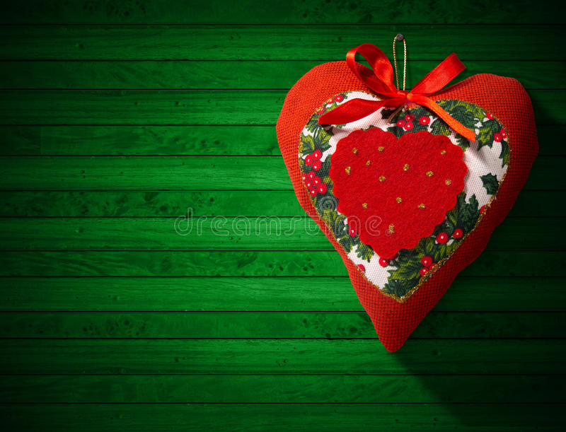 Christmas Heart Decoration on Wooden Wall. Christmas heart, red, white and green hanging on green wooden wall with shadows stock illustration