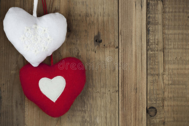Christmas Heart Decorations over Timber. Two Christmas heart-shaped decorations, over grunge timber stock photo