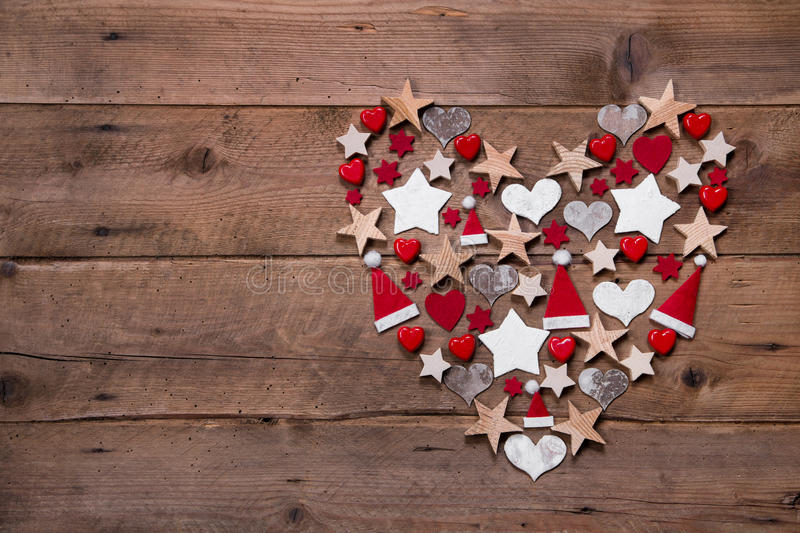 Christmas heart on a wooden background with different decoration. In red and white royalty free stock photography