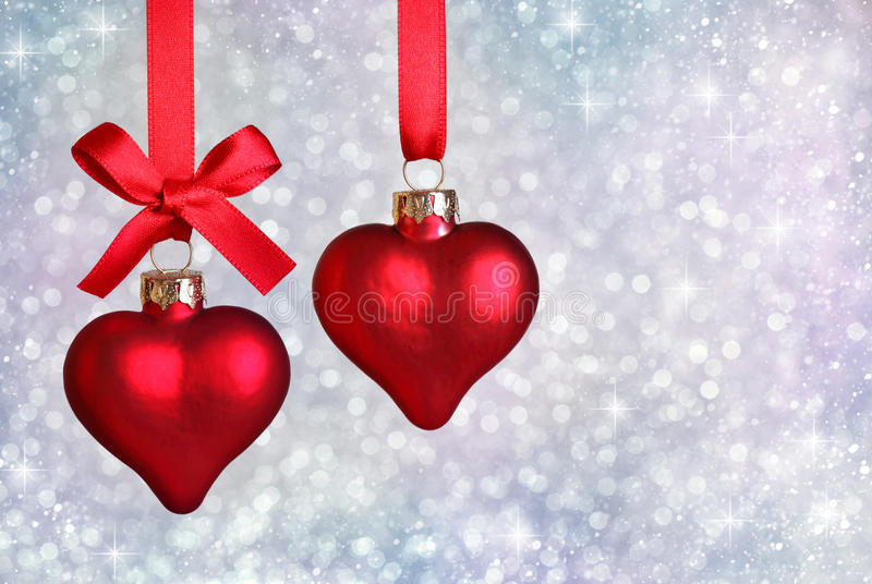 Christmas hearts. Hanging with ribbon on silver background