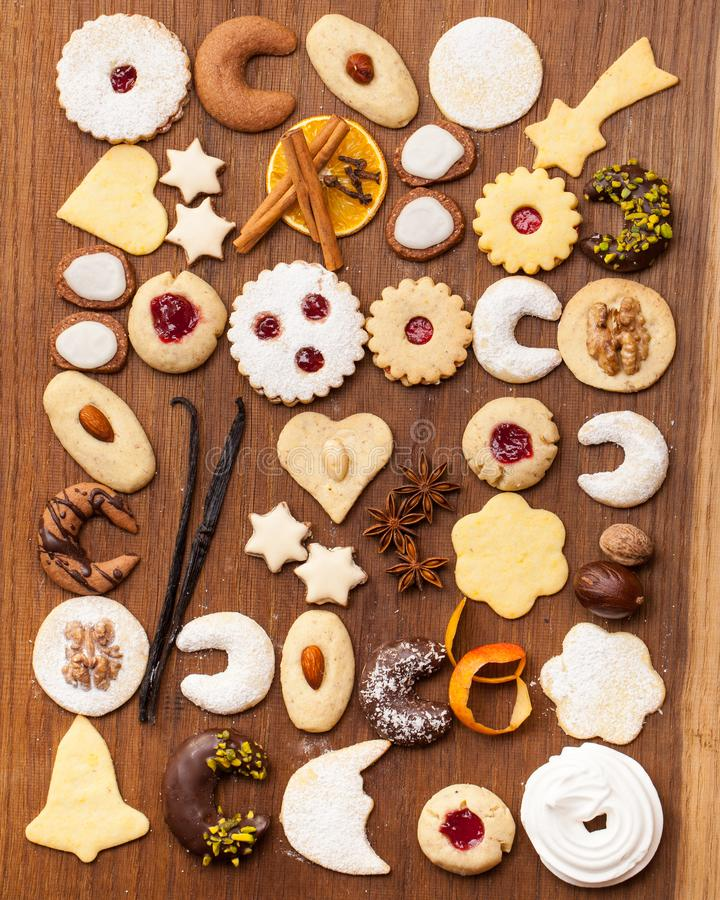 Many biscuits and spices on wooden background. Christmas is here: Many biscuits and spices on wooden background stock photo