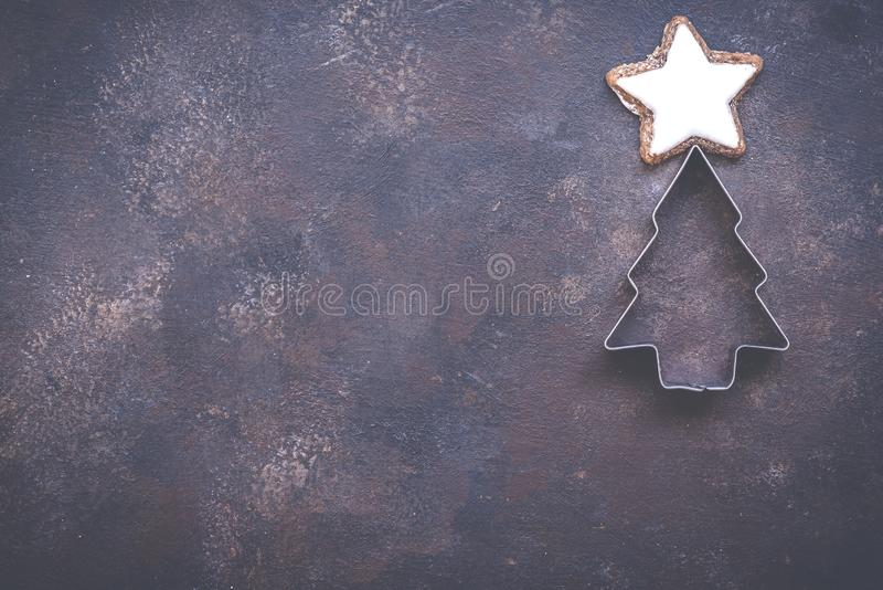 Christmas holiday background with cookie cutter tree on vintage style dark background. Concept of holiday coziness, top. Christmas holiday background with cookie stock image