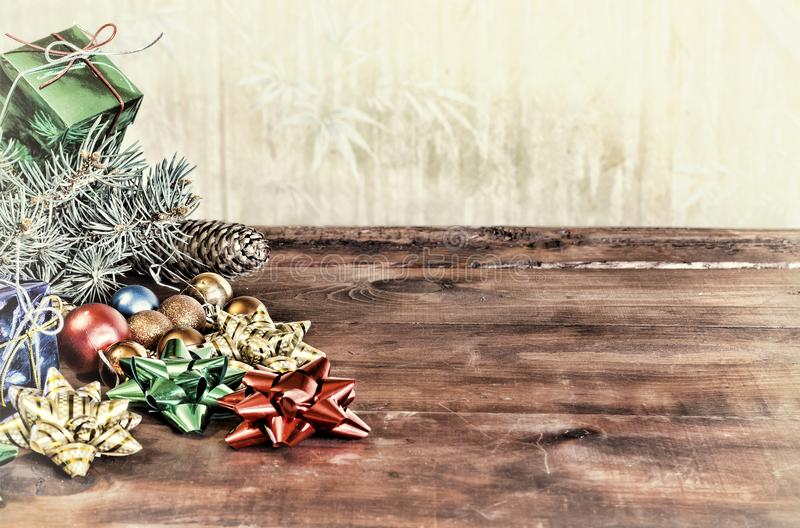 Christmas holiday background with empty wooden deck with a table decorated with a Christmas tree branch fluffy and colorful gift b royalty free stock photo