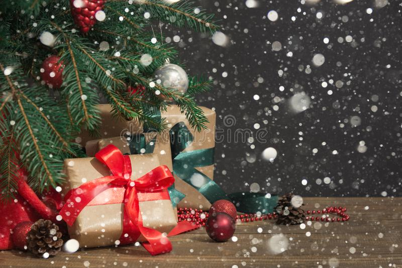 Christmas holiday background. Gifts with a red ribbon, Santa`s hat and decor under a Christmas tree on a wooden board. stock photos