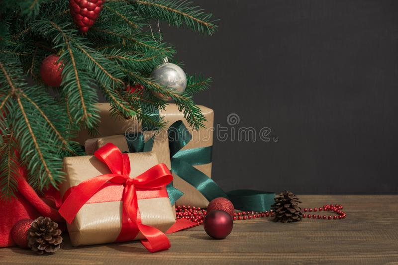 Christmas holiday background. Gifts with a red ribbon, Santa`s hat and decor under a Christmas tree on a wooden board. Close up. Copy space on chalkboard stock photo