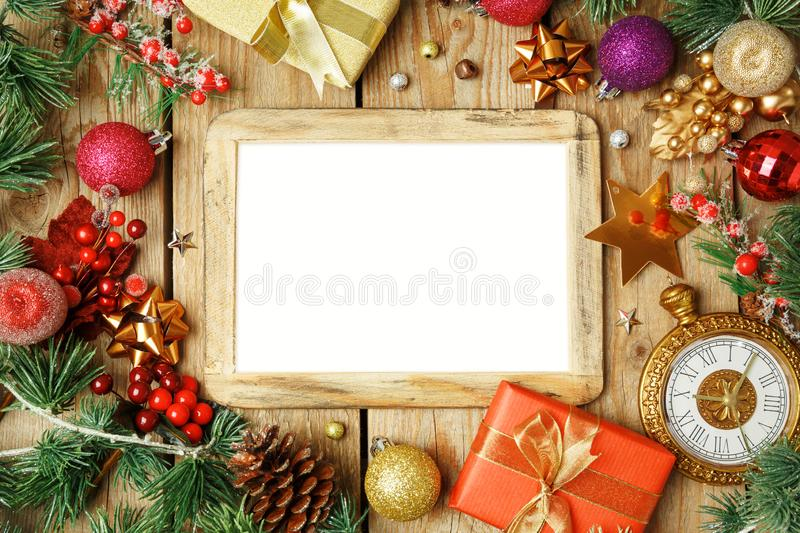 Christmas holiday background with photo frame, decorations and o. Rnaments on wooden table. Top view from above royalty free stock photos