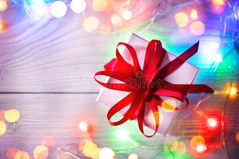 Christmas holiday background. Wrapped gift box with red silk ribbon and colorful lights garland over wooden background stock image