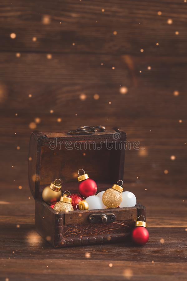 Christmas holiday balls in the old wooden chest on rustic background, postcard concept stock photography