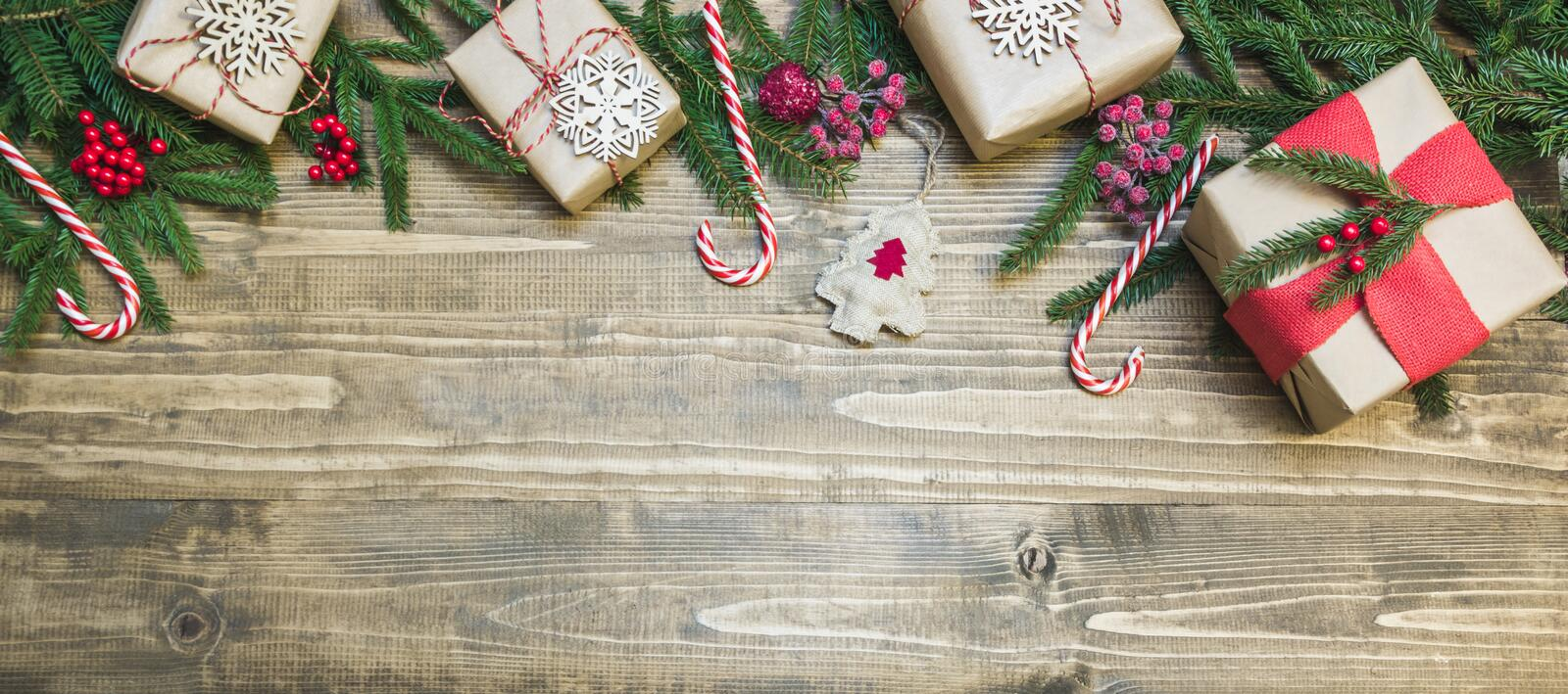 Christmas holiday banner - gifts, holly berries and decoration on wooden board. Holiday card. Top view. royalty free stock photos