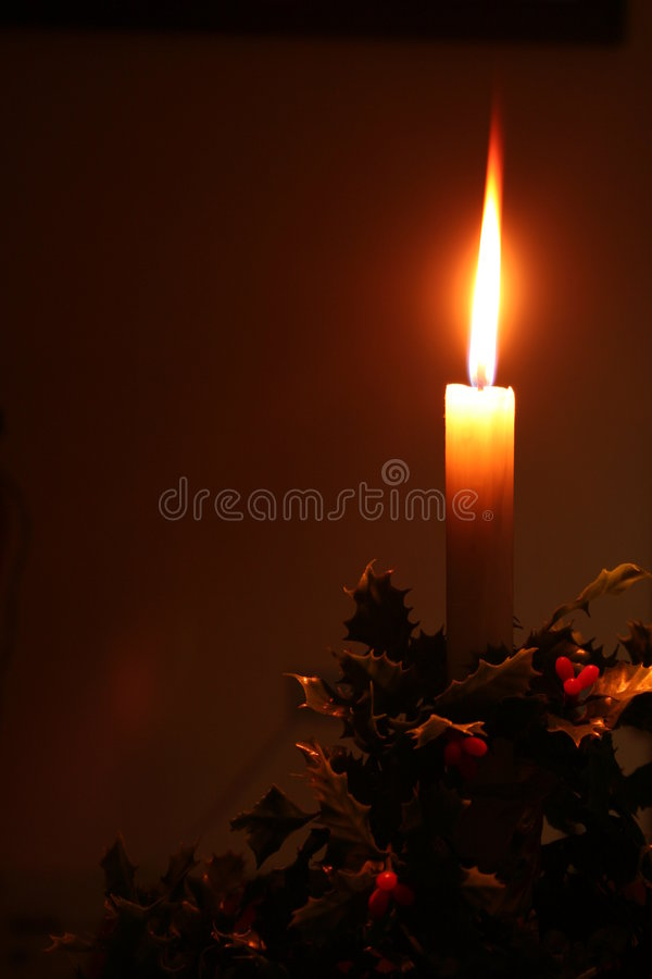 Christmas holiday candle. Beautiful candle with holly around base taken in a room only lit by the candle