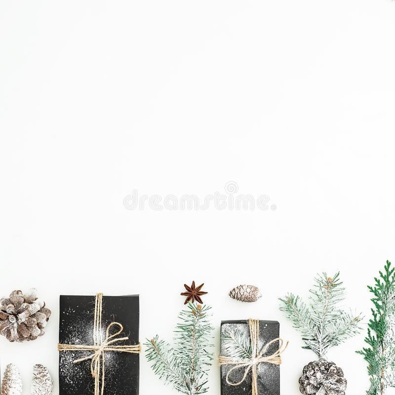 Christmas holiday composition of black gift box, fir branches and pine cones on white background. New year concept. Flat lay. Top royalty free stock image
