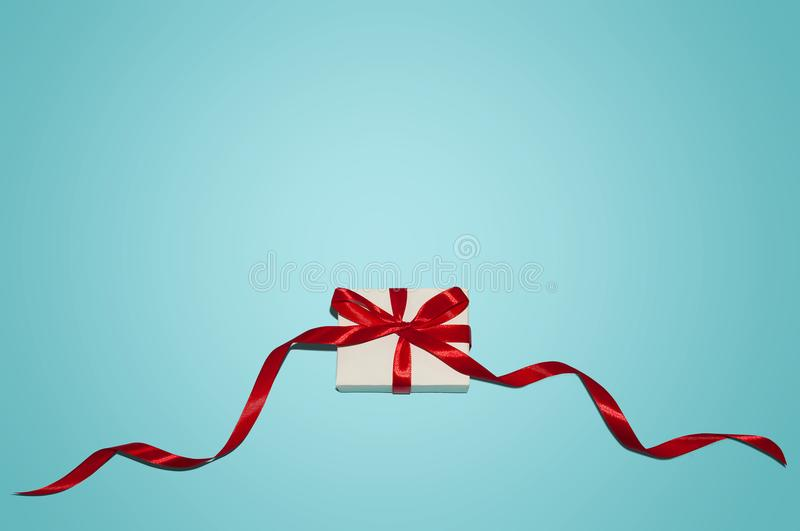 Christmas Holiday Composition. New Year Gift in White Box with Red Ribbon on Blue Background Flat Lay Top View with Copy Space royalty free stock image