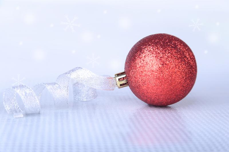 Christmas or holiday composition with red silver balls on billowy feathers with snow and snowflakes. royalty free stock photo