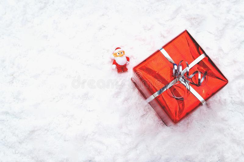 Christmas holiday decor with Santa Claus and gift. New year decoration background on the artificial snow, flat lay, top view, horizontal, copy space royalty free stock photos