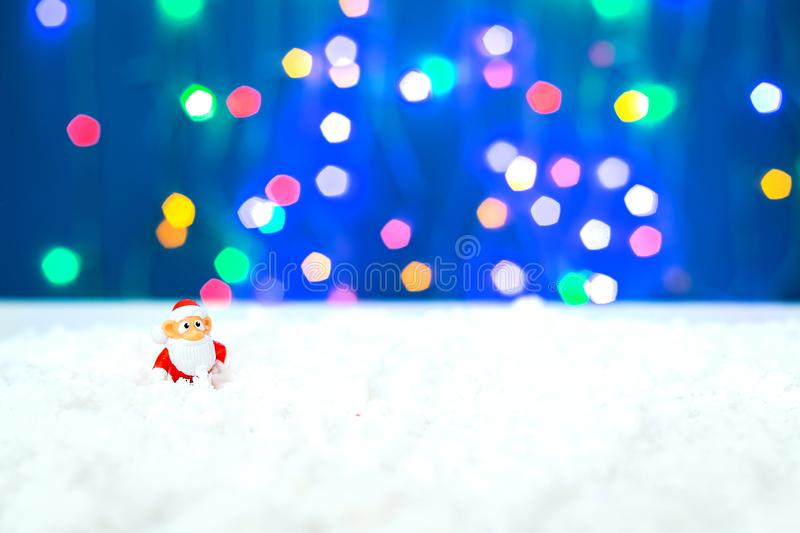 Christmas holiday decor with Santa Claus and lights. New year decoration background on the artificial snow, flat lay, top view, horizontal, copy space stock photo