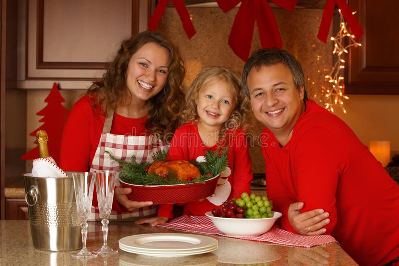 Christmas Holiday Family portrait. Happy family of three preparing Thanksgiving dinner, with turkey and champagne at home. New Year Eve stock photos