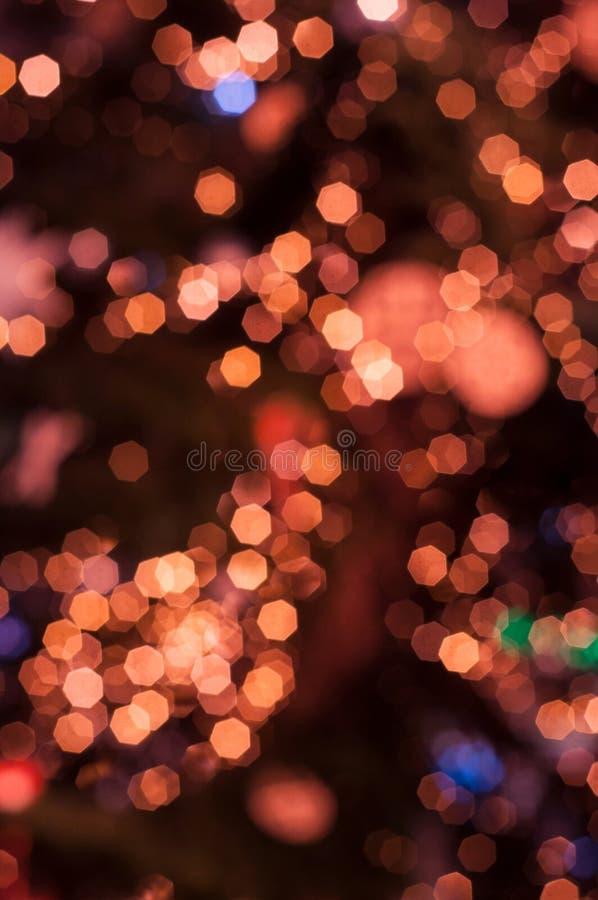 Festive glittering defocused orange background. Christmas holiday festive glittering defocused orange background with bokeh lights stock photo
