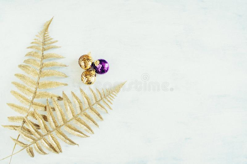 Christmas holiday festive theme with golden violet Christmas ornament and gold decorative fern leaves stock photo