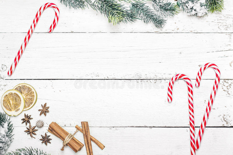 Christmas holiday frame with candy canes and fir branches on woo stock photo