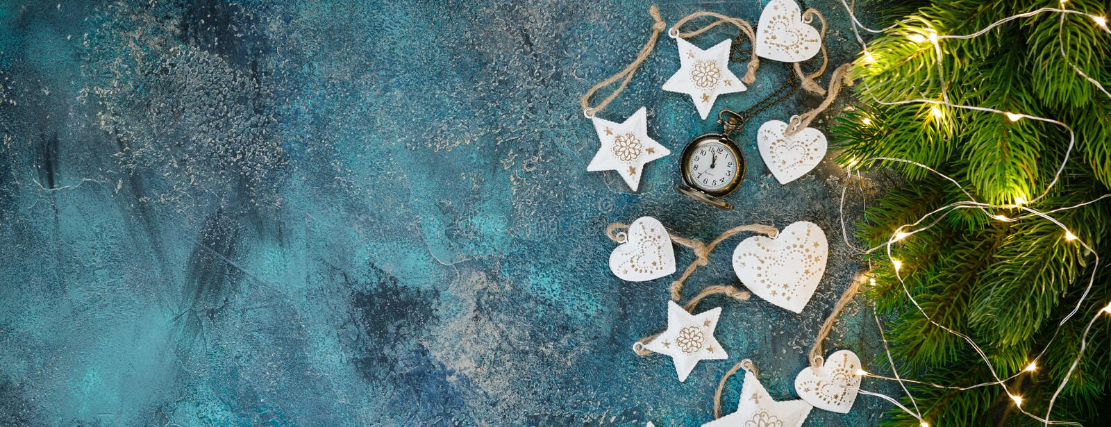 Christmas holiday frame with festive decorations - white metal hearts and old pjcket wathes on old blue background. Christmas royalty free stock photos