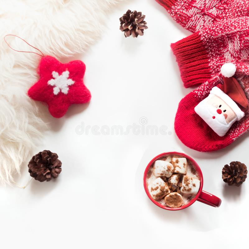 Christmas holiday hot chocolate with marshmallow, cone, white fur, red felt star, knitted socks on white background. stock photo