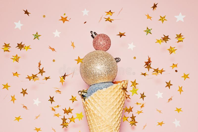 Christmas holiday inspiration concept. Creative ice cream made from Xmas decoration in waffle cone on pink background with gold royalty free stock photography