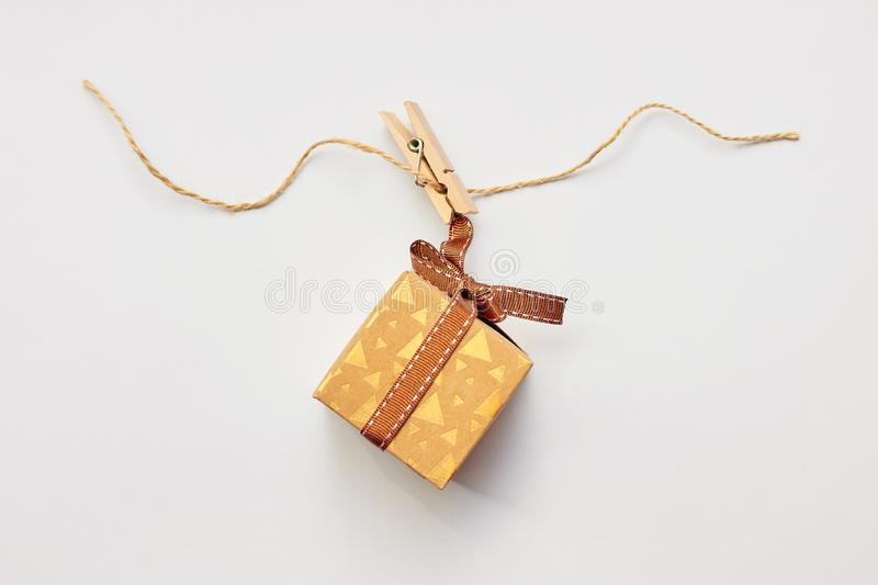 Christmas or Holiday present concept. Craft cardboard gift box hanging on clothes peg over white background. Flat lay, top view royalty free stock photo