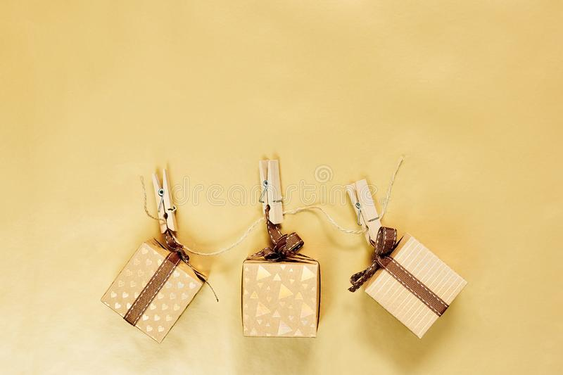 Christmas or Holiday present concept. Craft cardboard gift boxes hanging on clothes pegs over golden background. Flat lay, top view with copy space stock image