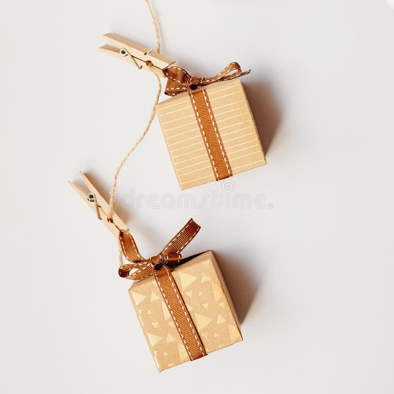 Christmas or Holiday present concept. Craft cardboard gift boxes hanging on clothes pegs over white background. Flat lay, top view stock photography