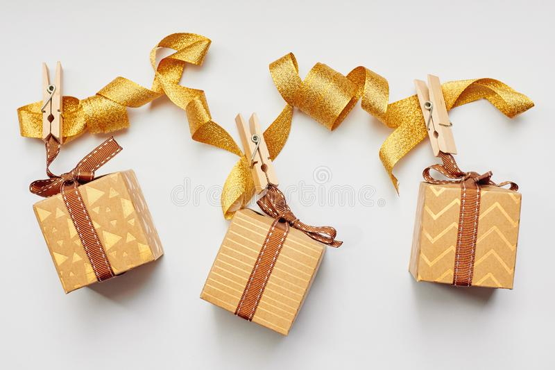 Christmas or Holiday present concept. Craft cardboard gift boxes hanging on clothes pegs over white background. Flat lay, top view stock photo