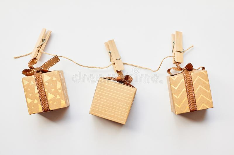 Christmas or Holiday present concept. Craft cardboard gift boxes hanging on clothes pegs over white background. Flat lay, top view royalty free stock photography