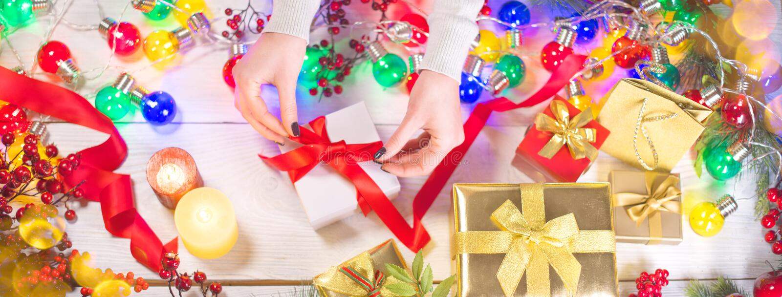 Christmas holiday scene. Person wrapping gift boxes on Xmas wooden background. Winter holiday backdrop stock photo