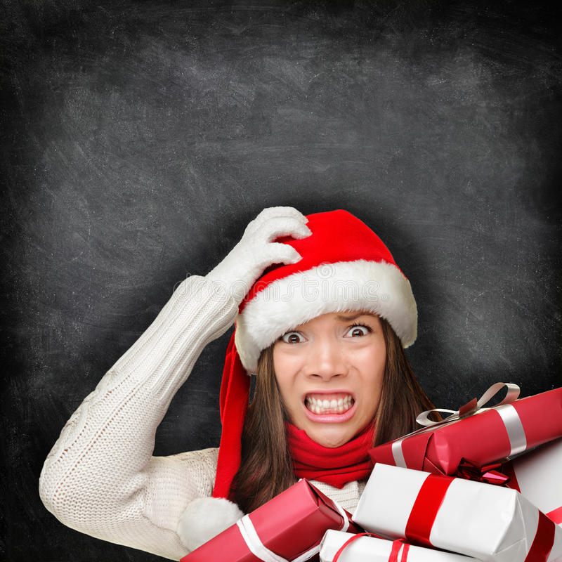 Christmas holiday stress - stressed gift woman. Christmas holiday stress. Stressed woman shopping for gifts holding christmas presents wearing red santa hat royalty free stock photos
