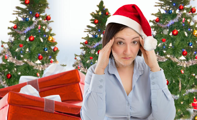 Christmas holiday stress. Stressed woman shopping for gifts of christmas with red santa hat looking angry and distressed stock image