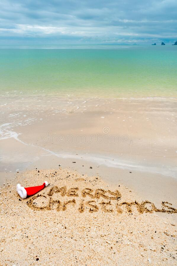 Christmas holiday tropical vacation concept, Merry Christmas written on tropical beach sand and sea background royalty free stock photo