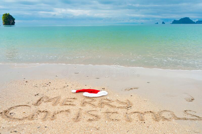 Christmas holiday tropical vacation concept, Merry Christmas written on tropical beach sand and sea background royalty free stock image