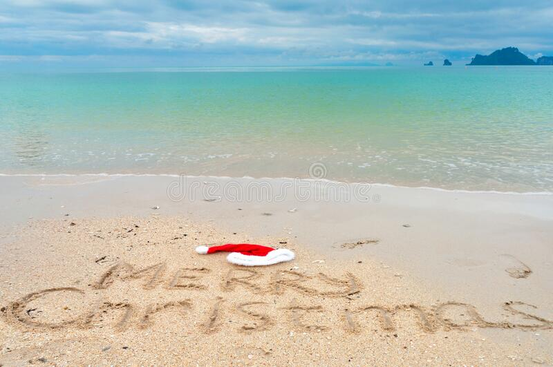 Christmas holiday tropical vacation concept, Merry Christmas written on tropical beach sand and sea background royalty free stock photography