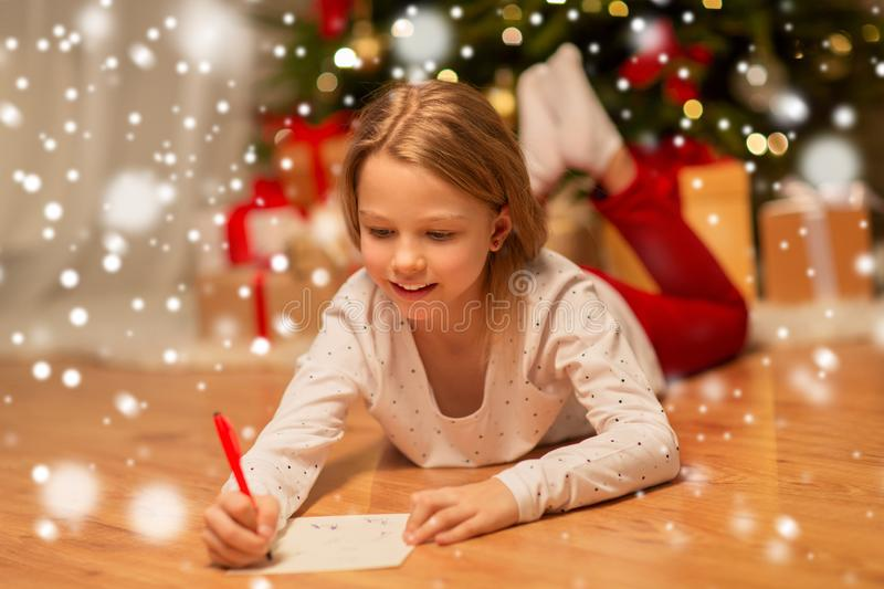 Smiling girl writing christmas wish list at home. Christmas, holidays and childhood concept - smiling girl writing wish list or letter to santa at home royalty free stock images