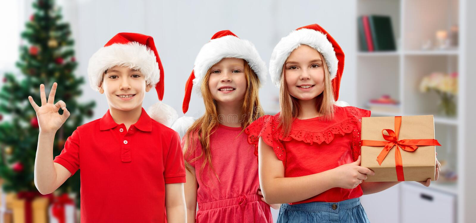 Children in santa helper hats with christmas gift. Christmas, holidays and childhood concept - smiling little children in santa helper hats with gift box showing royalty free stock photos