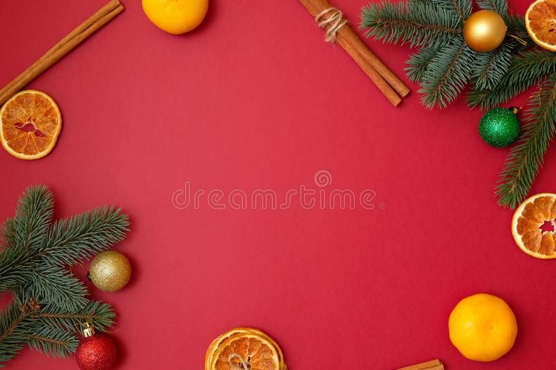 Christmas holidays composition on red background with copy space for your text. Xmas tree branches in the corners, dried oranges, stock photos