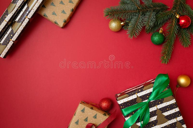 Christmas holidays composition on red background with copy space for your text. Xmas tree fir branches with ball in the corner, gi. Ft box. Xmas backdrop for royalty free stock photos