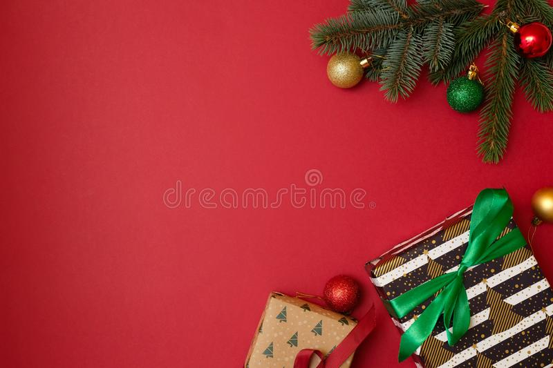 Christmas holidays composition on red background with copy space for your text. Xmas tree branches in the corners, dried oranges, royalty free stock photography