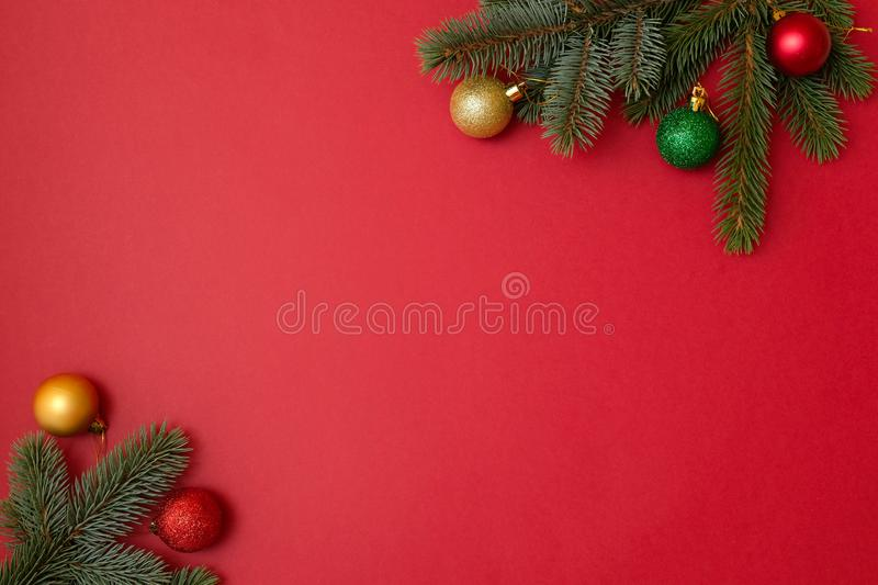 Christmas holidays composition on red background with copy space for your text. Xmas tree fir branches with balls in the corners,. Xmas backdrop for greeting royalty free stock photos