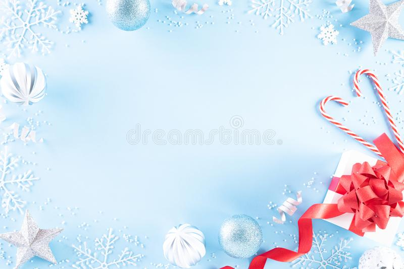 Christmas holidays composition Top view of red gift box with Christmas decoration snowflakes, star, candy cane and balls on light. Blue pastel background with royalty free stock image