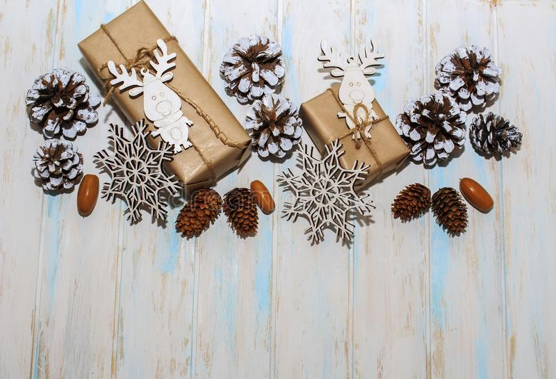 Christmas holidays composition on white wooden background. Craft boxes of gifts, wooden deer and snowflakes, fir cones, pine cones stock images