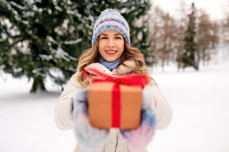 Happy young woman with christmas gift in winter stock image
