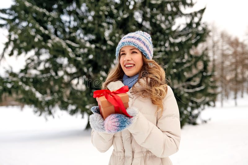 Happy young woman with christmas gift in winter stock photography