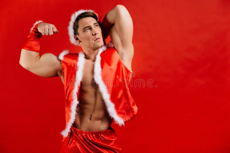 Christmas holidays. strong santa claus wearing hat. Young muscular man. red background. stock photography