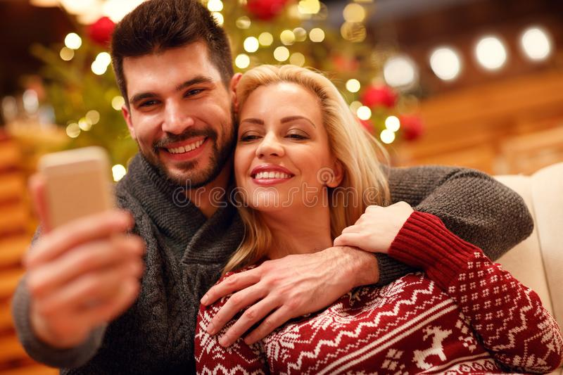 Christmas, holidays, technology and people concept - couple taking selfie. royalty free stock photo